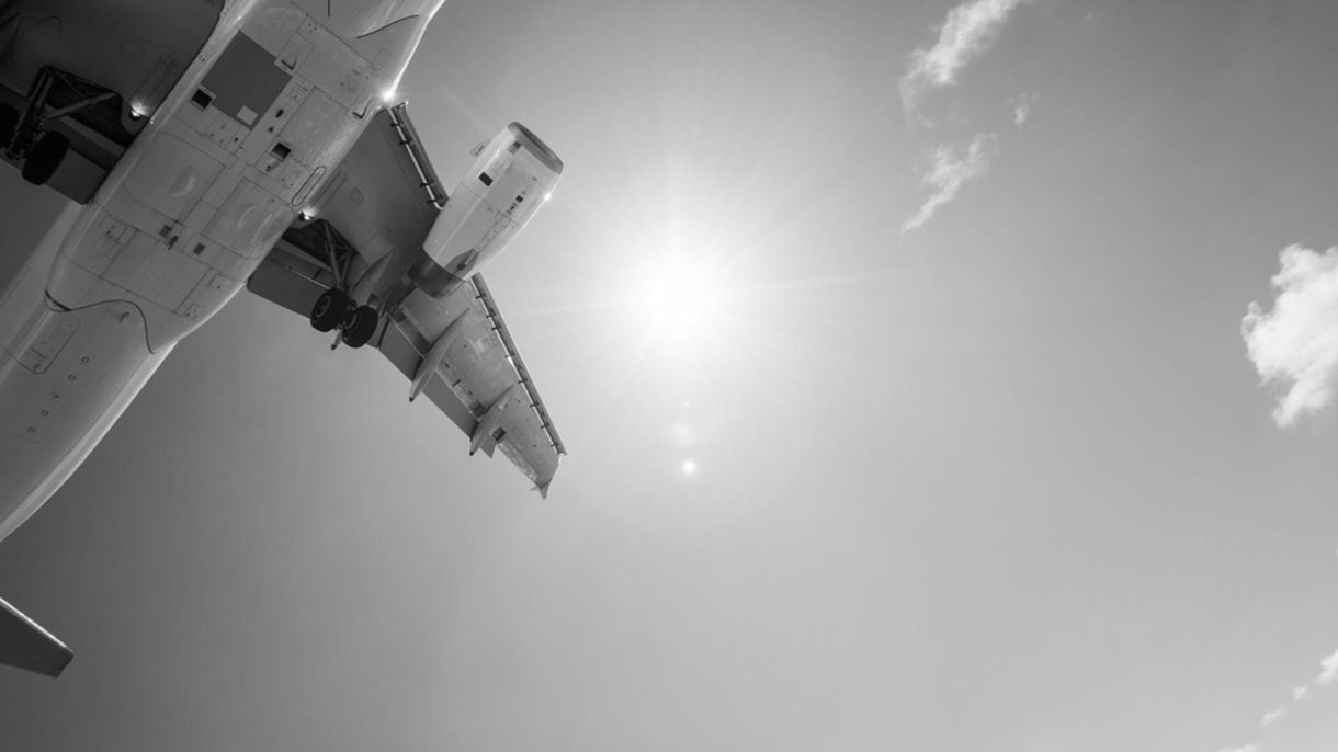 Greyscale image of a flying aeroplane
